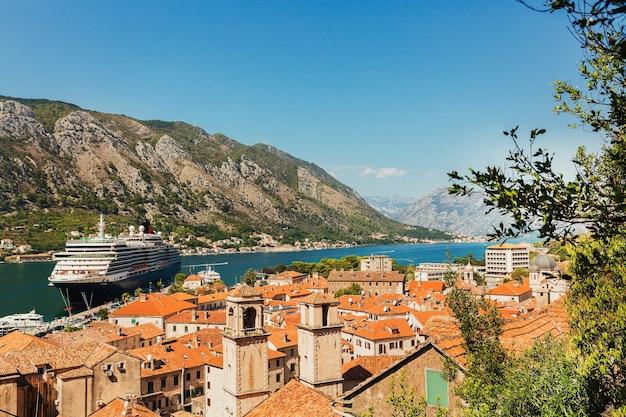 Kleurrijk landschap met oranje daken van de oude stad, boten en groot cruiseschip in jachthavenbaai, zee, bergen, blauwe hemel. bovenaanzicht van de baai van kotor, montenegro Premium Foto