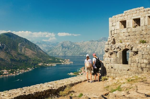 Kleurrijk landschap met oude muren in oude citadel, bergen, zee, blauwe hemel. bovenaanzicht van de baai van kotor van middeleeuwse vesting. historisch monument in montenegro Premium Foto