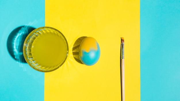 Kleurrijk paasei met verfborstel en glas water op heldere lijst Gratis Foto