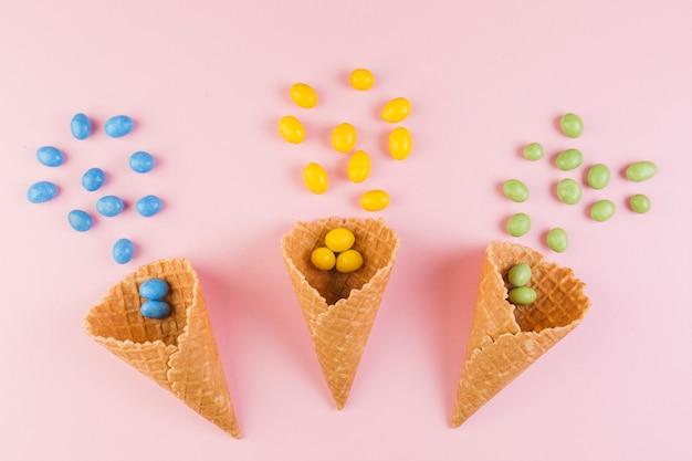 Kleurrijk suikergoed die van de wafelkegel van het roomijs op roze achtergrond morsen Gratis Foto