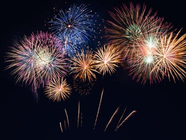 Kleurrijk vuurwerk op de zwarte hemelachtergrond met copyspace. viering en verjaardag Premium Foto