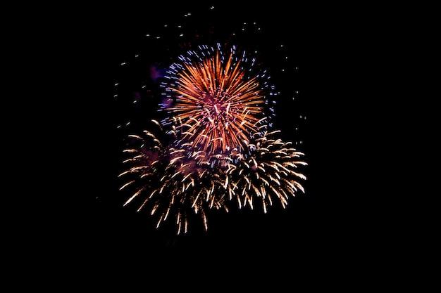 Kleurrijk vuurwerk tegen een zwarte nachthemel. vuurwerk voor het nieuwe jaar. mooi kleurrijk vuurwerk op het stedelijke meer voor viering Premium Foto