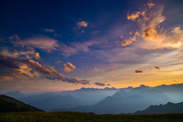 Kleurrijk zonlicht op de majestueuze bergtoppen, groene weiden en mistige valleien van de italiaanse alpen. gouden cloudscape bij zonsondergang. Premium Foto