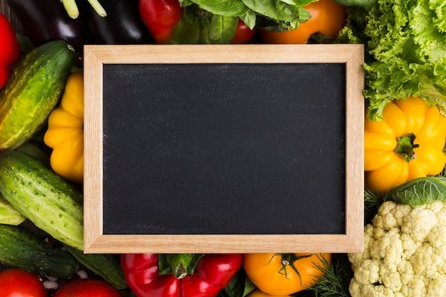 Kleurrijke achtergrond met groenten en bord Gratis Foto
