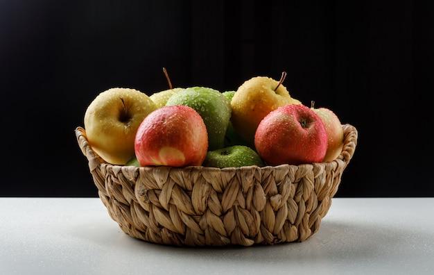 Kleurrijke appels in een rieten mand op zwart-wit Gratis Foto