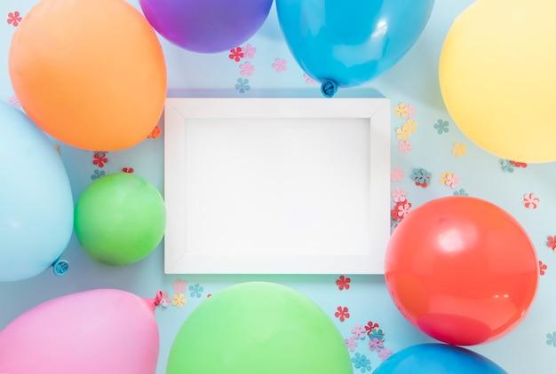 Kleurrijke ballonnen rond leeg frame Gratis Foto