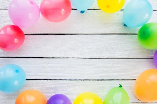 Kleurrijke ballonnen versierd op houten witte plank Gratis Foto