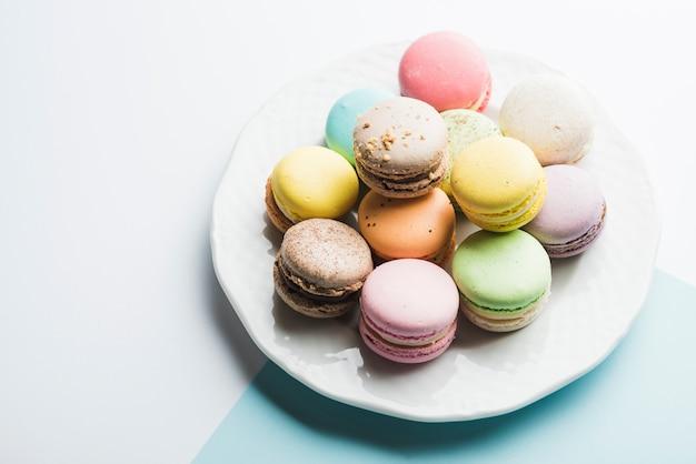 Kleurrijke bitterkoekjes op witte plaat tegen witte achtergrond Gratis Foto
