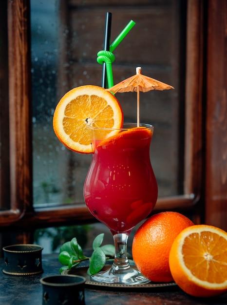 Kleurrijke cocktail met stukjes sinaasappel, cocktailparaplu, groen en zwart stro Gratis Foto