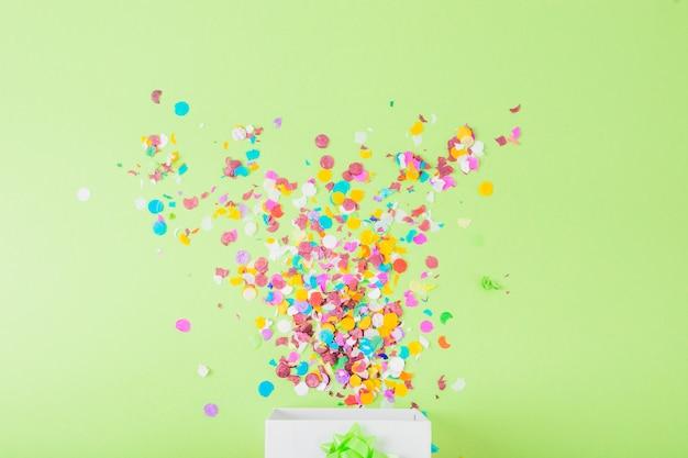 Kleurrijke confettien die in de witte doos over de groene achtergrond vallen Gratis Foto