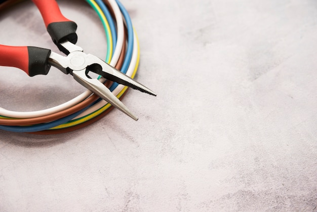 Kleurrijke draad en tang op grijze concrete achtergrond Premium Foto