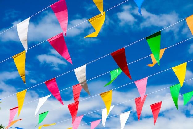 Kleurrijke driehoekige vlaglijn die zich door wind op blauwe hemel witte wolk beweegt Premium Foto