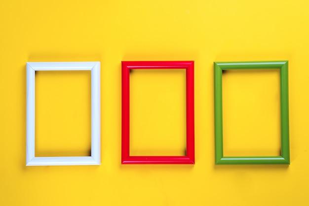 Kleurrijke foto- of fotolijsten op een geel papier achtergrond. copyspace plat lag Premium Foto