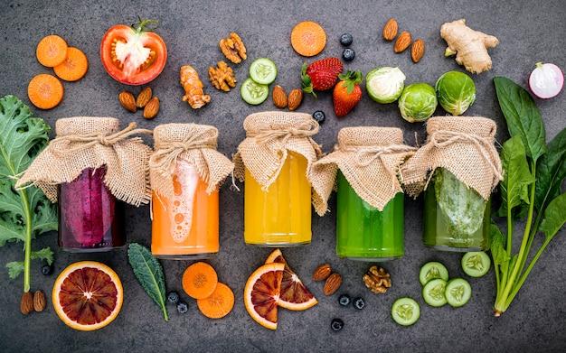 Kleurrijke gezonde smoothies en sappen in flessen met vers tropisch fruit en superfoods op donkere steen Premium Foto