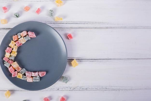 Kleurrijke halve maan gemaakt met lukum op grijze plaat over de witte houten tafel Gratis Foto