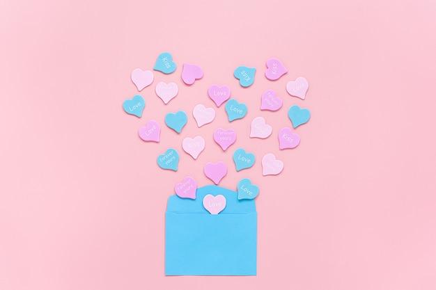 Kleurrijke harten met tekst liefde, kus, voor altijd vliegen in de vorm van een hart van blauwe papieren envelop op roze Premium Foto