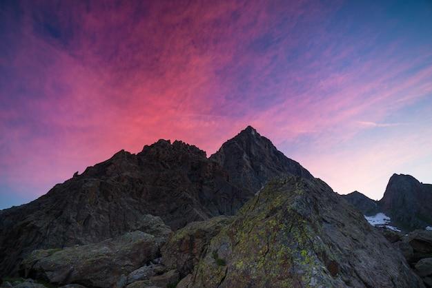 Kleurrijke hemel voorbij rotsachtige bergpiek op de italiaanse alpen bij schemer Premium Foto