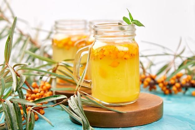 Kleurrijke hete duindoornthee met gember en honing Premium Foto
