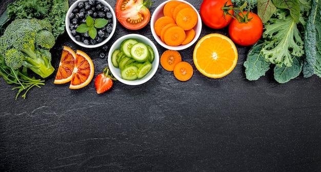Kleurrijke ingrediënten voor gezonde smoothies en sappen op donkere steen Premium Foto