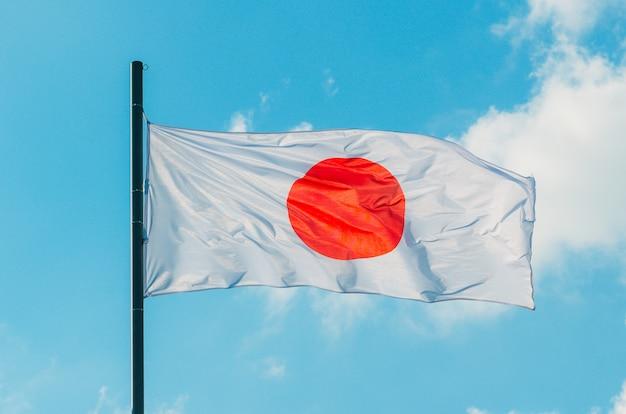 Kleurrijke japan vlag zwaaien op blauwe hemel. Premium Foto