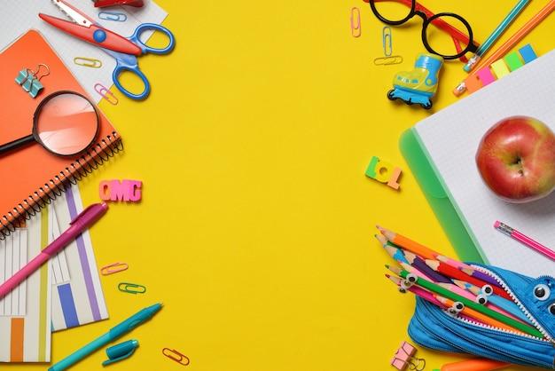 Kleurrijke kantoor- en studentenbenodigdheden op geel Premium Foto