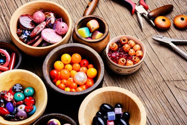 Kleurrijke kralen in houten kommen Premium Foto