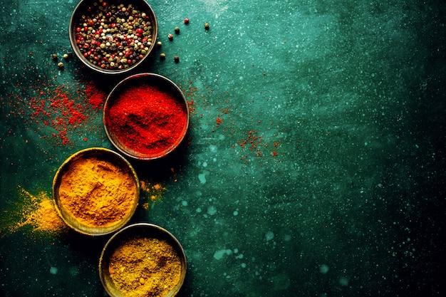 Kleurrijke kruiden op donkere tafel Gratis Foto