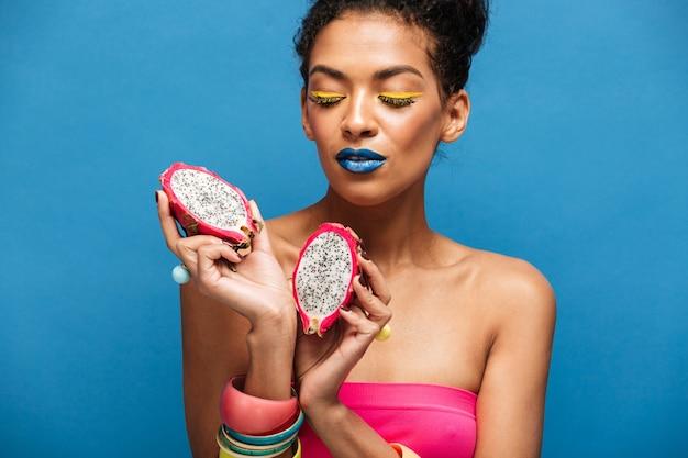 Kleurrijke mooie gemengd rasvrouw met heldere schoonheidsmiddelen die op gezicht rijpe pitahaya houden die in de helft in beide geïsoleerde handen wordt gesneden, over blauwe muur Gratis Foto