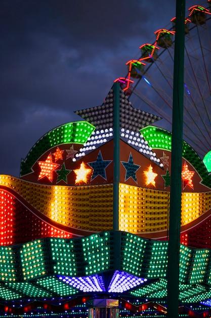 Kleurrijke neonlichten in stervormen op de achtergrond van reuzenrad Gratis Foto