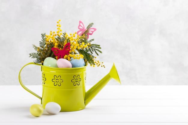 Kleurrijke paaseieren en mimosa bloemen Premium Foto