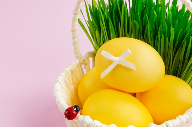 Kleurrijke paaseieren in een witte mand met decoratieve greens Premium Foto