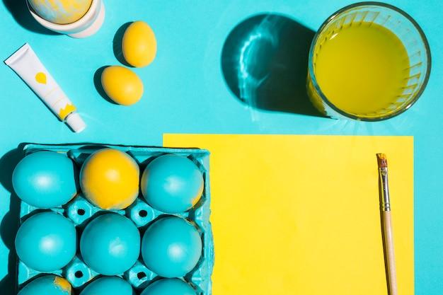 Kleurrijke paaseieren in rek met verfborstel, glas water en document Gratis Foto