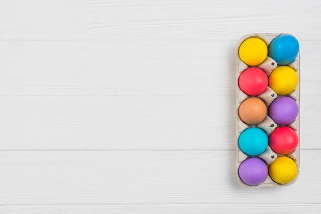 Kleurrijke paaseieren in rek op houten lijst Gratis Foto