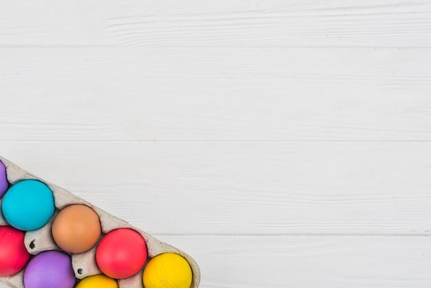 Kleurrijke paaseieren in rek op lijst Gratis Foto