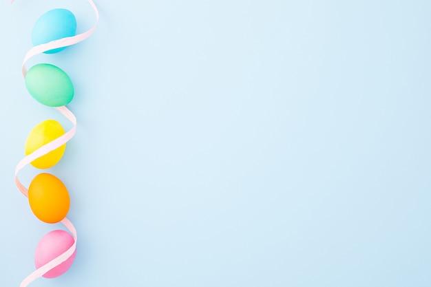 Kleurrijke paaseieren met roze lint op een lichtblauwe achtergrond. plat leggen. bovenaanzicht kopieer ruimte Premium Foto