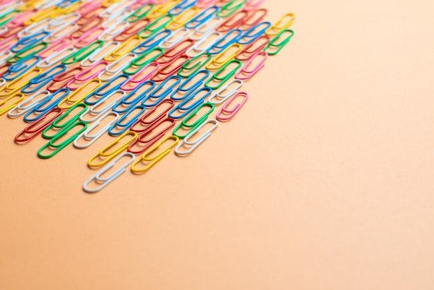 Kleurrijke paperclips op oranje achtergrond. terug naar school. verschillende kleuren draadpluggen zijn één type kantoormateriaal. copyspace Premium Foto