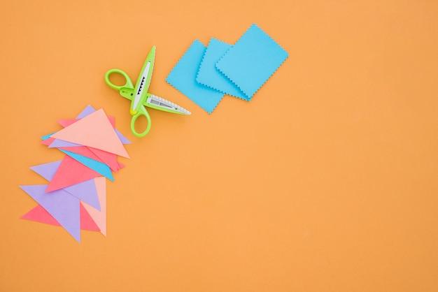 Kleurrijke papier en schaar op gekleurde achtergrond Gratis Foto