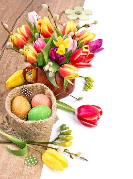 Kleurrijke pasen-grens met bos van tulpen en geschilderde eieren op hout, Premium Foto