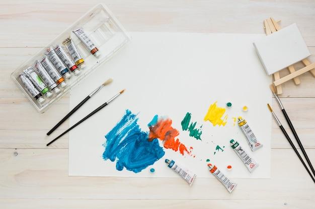 Kleurrijke penseelstreek op wit blad met schildermateriaal Gratis Foto