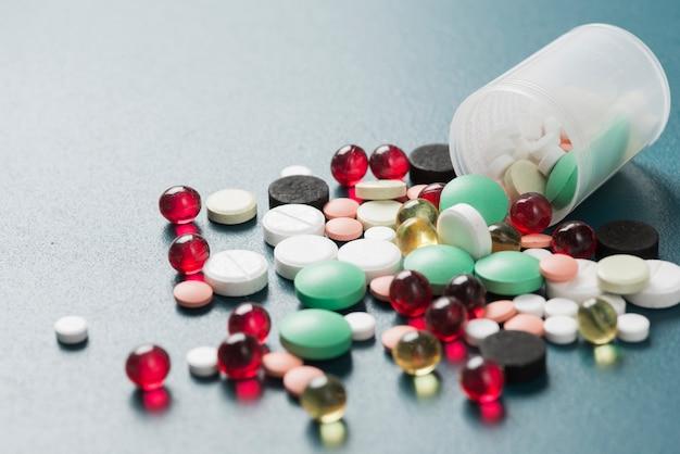 Kleurrijke pillen en capsules in de beker Gratis Foto