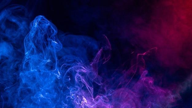 Kleurrijke rode en blauwe kleurenrook die op zwarte achtergrond wordt geïsoleerd Premium Foto