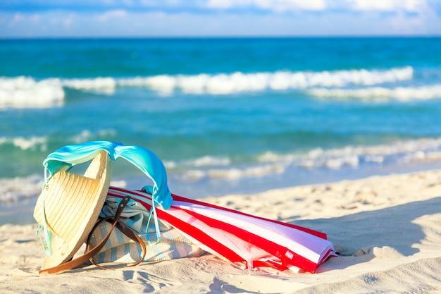 Kleurrijke rode en witte paraplu met strohoed, strandtas en blauwe bikini beha badpak tegen de oceaan strand met prachtige blauwe lucht en wolken Premium Foto