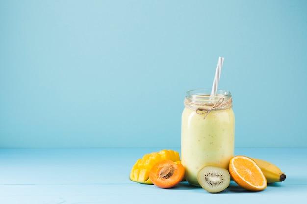Kleurrijke smoothie en fruitachtergrond Premium Foto