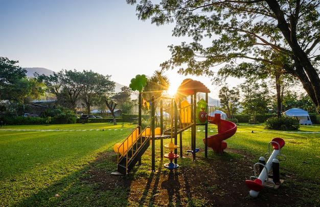 Kleurrijke speelplaats en zonsopgang op werf in het park Premium Foto