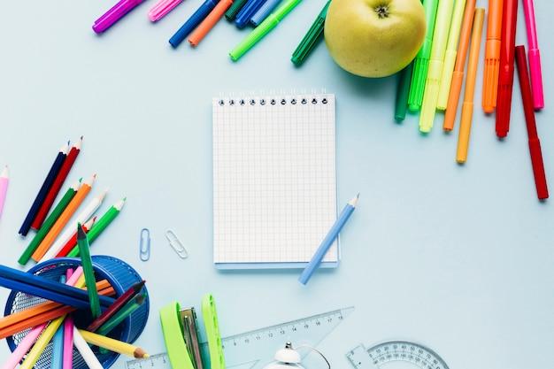 Kleurrijke tekenhulpmiddelen die rond lege blocnote op blauw bureau worden verspreid Gratis Foto