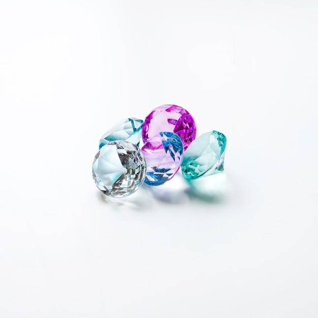 Kleurrijke transparante diamanten die op witte achtergrond worden geïsoleerd Gratis Foto