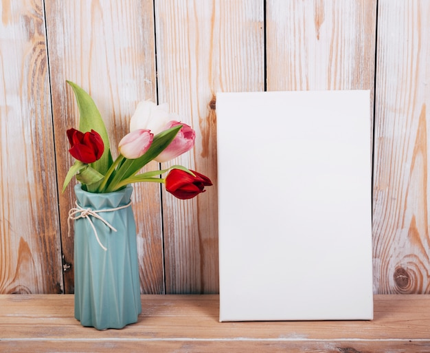 Kleurrijke tulpenbloemen in vaas met lege aanplakbiljet houten achtergrond Gratis Foto