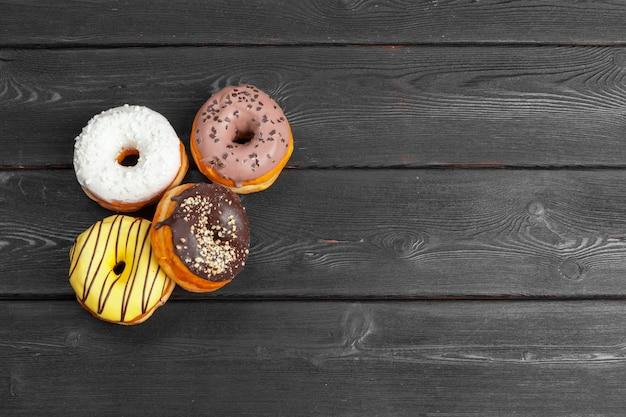 Kleurrijke verse donuts op donkere zwarte houten oppervlakteachtergrond Premium Foto
