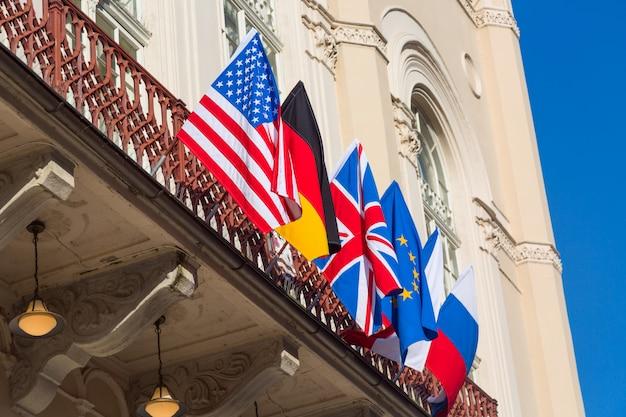 Kleurrijke vlaggen van verschillende landen bij het voortbouwen tegen blauwe hemel. vs, rusland, eu, groot-brittannië, duitsland Premium Foto