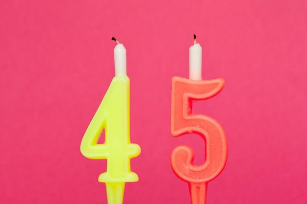 Kleurrijke wax verjaardagskaars op roze Premium Foto